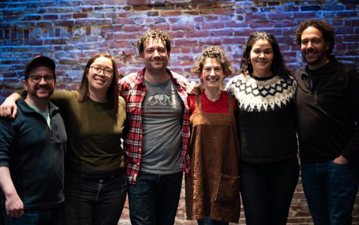 Five smiling people stand in front of a brick wall with the arms around each others shoulders.